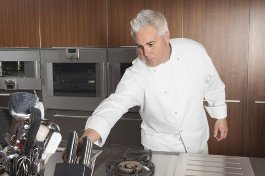 Male chef leaning for knife in commercial kitchen