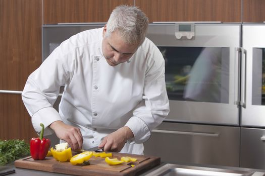 Male chef slicing bell pepper in commercial kitchen