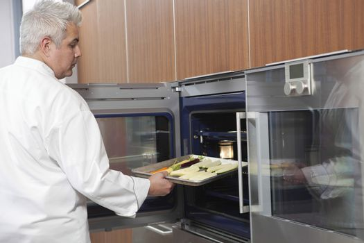 Side view of male chef placing baking tray in oven