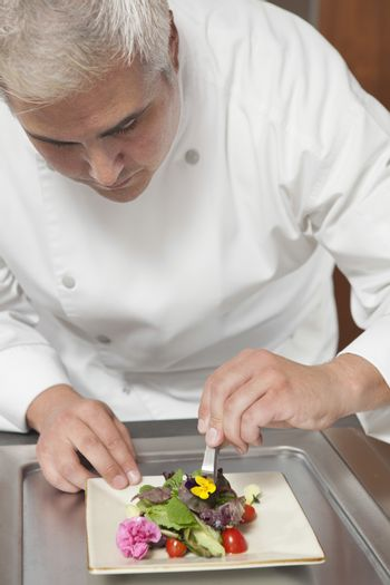 Male chef arranging edible flowers on salad in commercial kitchen