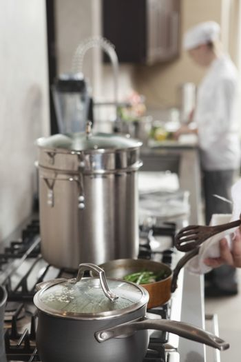 Chef heating saucepan on stove with coworker in background