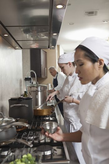 Three chefs working side by side in busy commercial kitchen