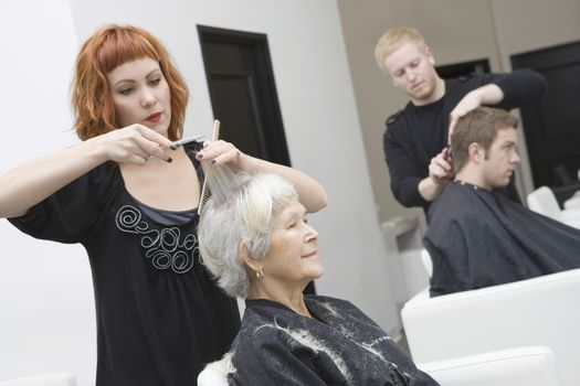 Hairdressers giving haircut to customers in unisex salon