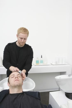 Male client has hair shampooed in unisex hair salon