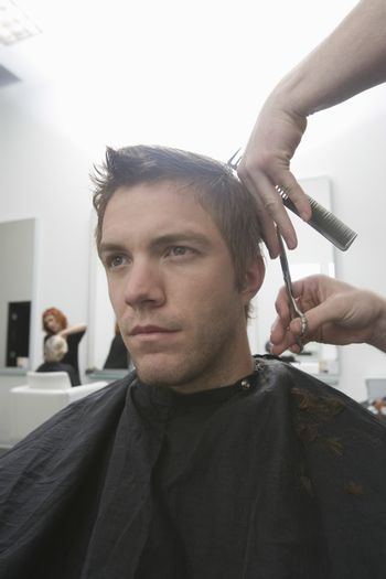 Handsome young man getting haircut in hair salon