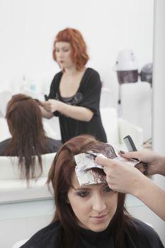 Colourist places foils in hair