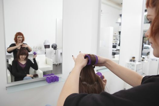 Stylist puts rollers in clients hair