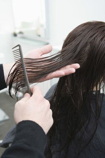 Wet hair is combed out in hair salon