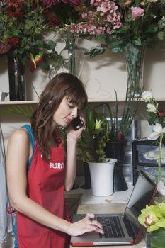 Florist checks orders on laptop computer