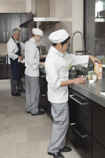 Three chefs working together in busy commercial kitchen