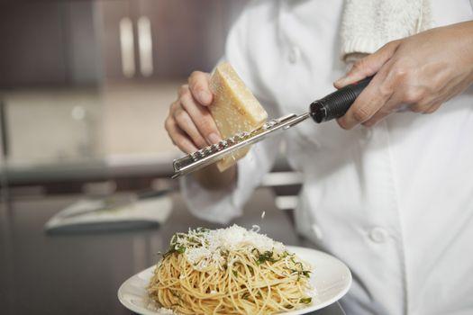 Grating parmesan onto spaghetti