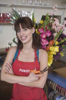 Florist stands with scissors in front of flower arrangement