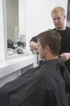 Man sitting in hairdressing robe   haircut