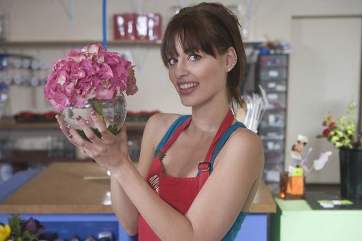 Florist holds up pink hydrangea