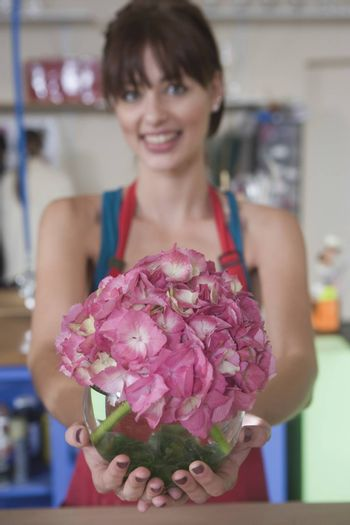 Florist holds out pink hydrangea