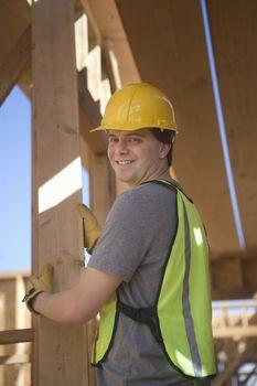 Labourer positioning plank of wood