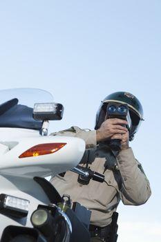 Patrol officer sits on motorcycle looking through speedometer