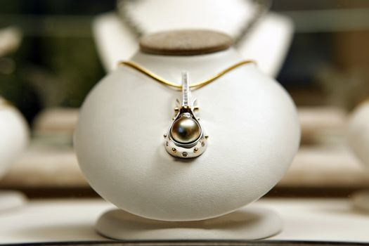 Round black pearl with diamonds on display at jewellery shop