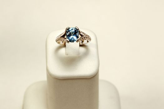 18k white gold ring with Aquamarine oval and diamonds over colored background
