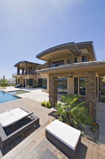 A house exterior with decking  lounge beds and a swimming pool