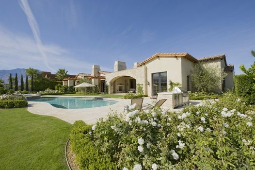 House exterior in daylight with a garden  plants  a swimming pool and hills in the far distance