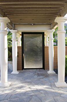 View of closed entrance door with pillars at yard