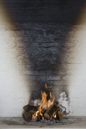 Burning wood against stained wall