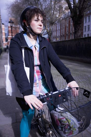 A female adult riding her bicycle
