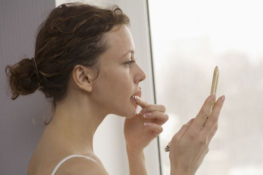 Mid adult woman stands applying lip gloss at window