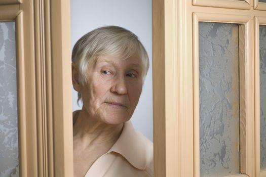 Elderly woman with short grey hair opening front door