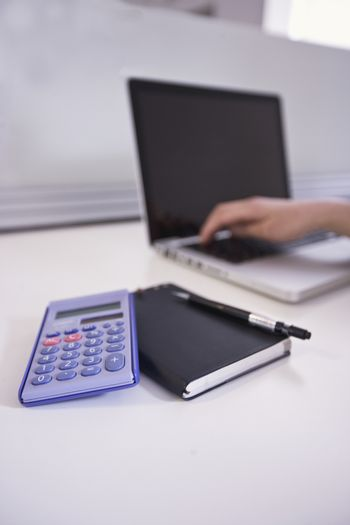 A notepad  calculator and laptop in an office