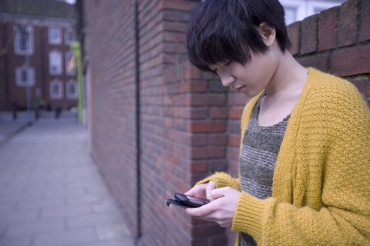 Young Asian woman text messaging as she leans on wall