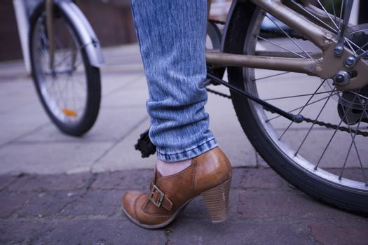 Low section of woman wearing brown high heeled shoe with bicycle