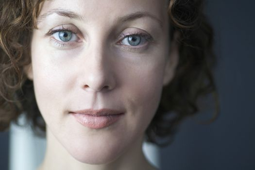 Mid adult woman looks directly at camera