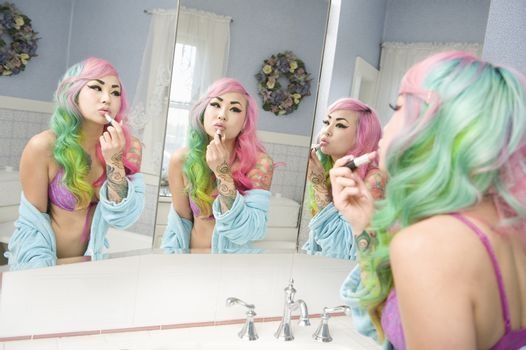 Young woman applying lipstick on her lips with multiple mirror reflections