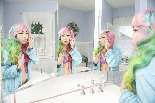 Young woman applying makeup with multiple mirror reflections