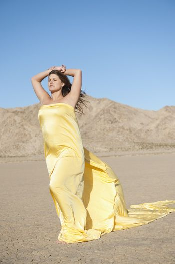 Young woman wrapped in yellow cloth on arid landscape