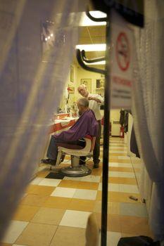 Barber giving a haircut to senior man in salon