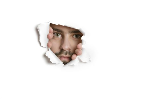 Portrait of a mid adult Caucasian man peeking from ripped paper hole