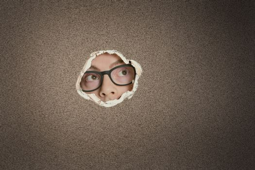 Mid adult Caucasian man looking away from ripped paper hole