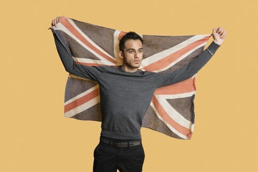 Young patriotic man lifting British flag over colored background