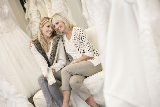Happy mother with arm around her daughter sitting in bridal store