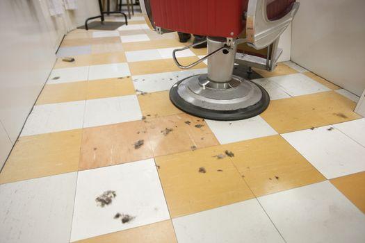 An empty barber shop with cut hair on floor
