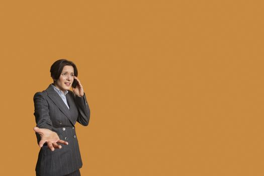 Annoyed woman talking on mobile phone with hand outstretched