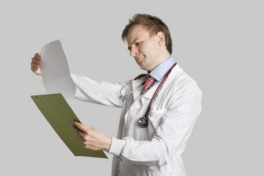 Male doctor in a lab coat reading medical records over gray background