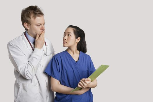 Serious Caucasian doctor and Asian nurse looking at each other over gray background