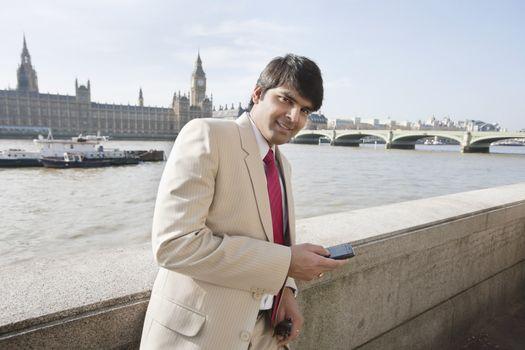 Portrait of an Indian businessman text messaging