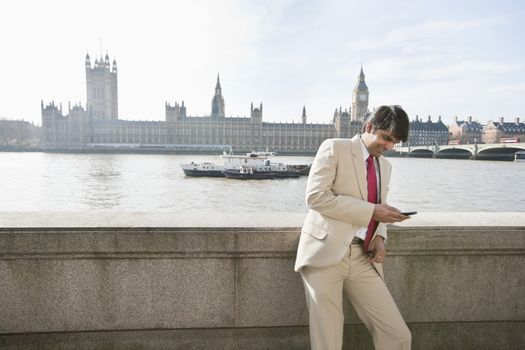 Indian businessman text messaging with watercraft and buildings in background