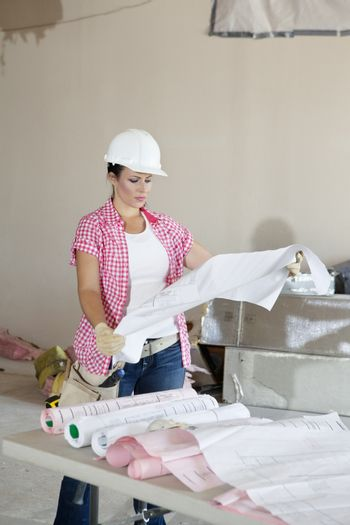 Young female contractor analyzing blueprints
