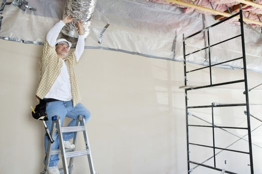 Architect on ladder working on ceiling